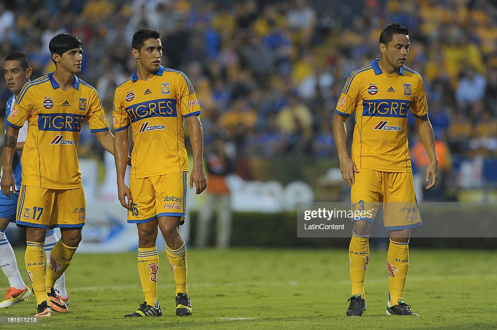 <a gi-track='captionPersonalityLinkClicked' href=/galleries/search?phrase=Alan+Pulido&family=editorial&specificpeople=5933954 ng-click='$event.stopPropagation()'>Alan Pulido</a>, Miguel Garcia and Juninho of Tigres during a match between Tigres UANL and Puebla FC as part of the Liga MX at Universitario stadium on September 21, 2013 in Monterrey, Mexico.