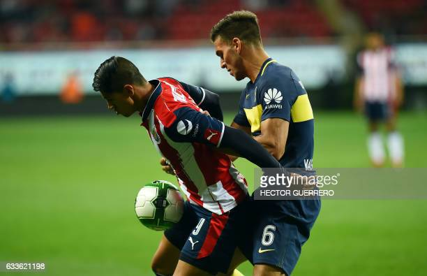 Alan Pulido of Guadalajara vies for the ball with Lisandro Magallan of Argentine club Boca Jr during a friendly football match at Chivas stadium on...