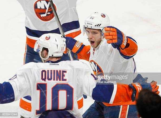 Alan Quine is congratulated by Nikolay Kulemin of the New York Islanders after scoring the game winning goal in the second overtime period against...