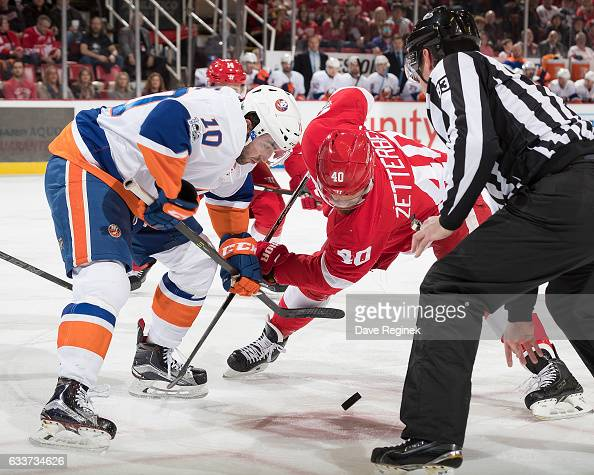 Alan Quine of the New York Islanders faces off against Henrik Zetterberg of the Detroit Red Wings during an NHL game at Joe Louis Arena on February 3...