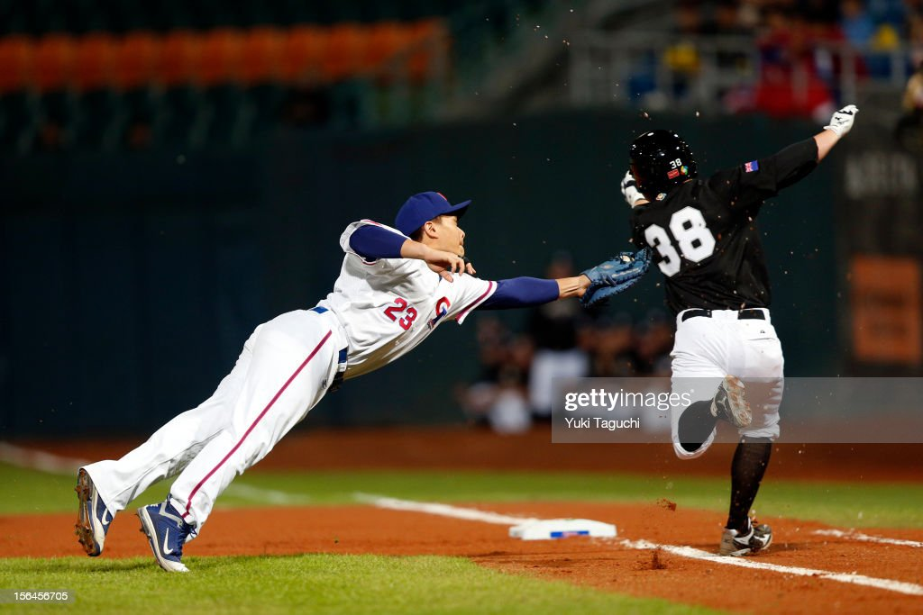 Alan Schoenberger of #38 of Team Thailand avoids the tag of Cheng-Ming Peng #23 of Team Chinese Taipei in the top of the first inning of Game 2 of the 2013 World Baseball Classic Qualifier between Team New Zealand and Team Chinese Taipei at Xinzhuang Stadium in New Taipei City, Taiwan on Thursday, November 15, 2012.