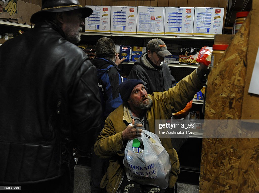 Alan Schram reaches for food items from his wheelchair at a Woonsocket food pantry. He was among scores of Woonsocket residents who got a bag of food at Bryan's Food Pantry (in the basement of St. Charles Church). He's a former truck driver (now disabled) and receives food stamps but it was the last day of the month and he (like many others) had run out of many food items. Many families and individuals in Woonsocket, Rhode Island are needy and take part in the SNAP (food stamps) program. Photo by Michael S. Williamson/The Washington Post via Getty Images