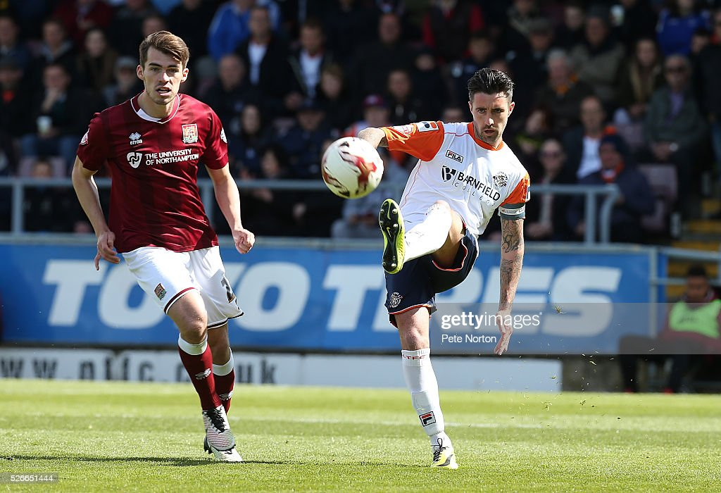 Alan Sheehan of Luton Town plays the ball watched by John Marquis of Northampton Town during the Sky Bet League Two match between Northampton Town and Luton Town at Sixfields Stadium on April 30, 2016 in Northampton, England.