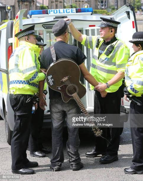 Alan Smart is led away by police after performing with his guitar with anti bedroom tax protesters outside the Albert Halls in Stirling on the first...