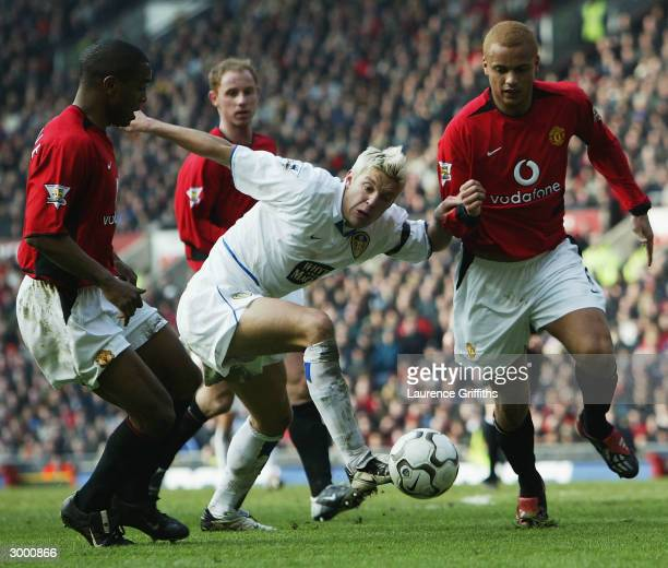 Alan Smith of Leeds clashes with Wes Brown and Quinton Fortune of Man Utd during the FA Barclaycard Premiership match between Manchester United and...