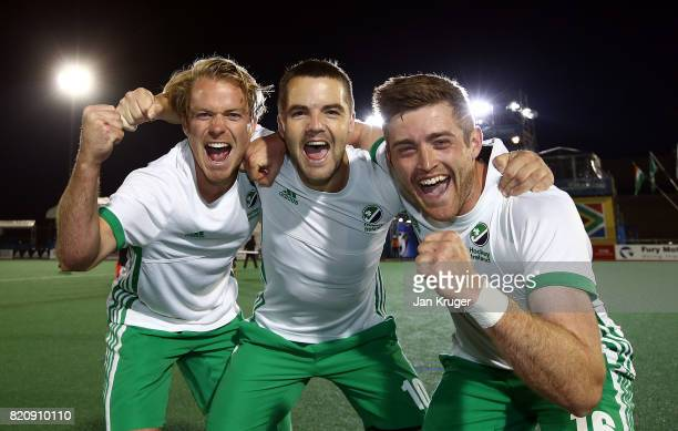 Alan Sothern of Ireland celebrates the win with team mates Stuart Loughrey and Shane O'Donoghue after the final whistle during day 8 of the FIH...