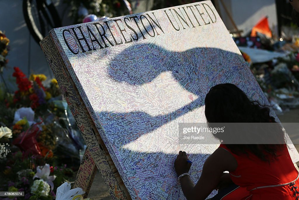 Alana Simmons leaves a message on a board set up in front of the Emanuel African Methodist Episcopal Church after a mass shooting at the church killed nine people, on June 22, 2015. 21-year-old Dylann Roof is suspected of killing nine people during a prayer meeting in the church in Charleston, which is one of the nation's oldest black churches.