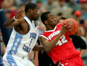 Alando Tucker of the Wisconsin Badgers tries to drive around Jackie Manuel of the North Carolina Tar Heels during their regional semifinal game at...