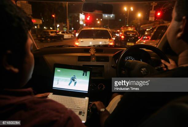 Alap Korde following the IPL match on his laptop while driving home from office with his friend Mandar Rahate
