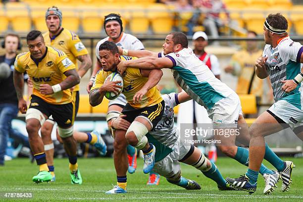 Alapati Leiua of the Hurricanes breaks the tackles of Caylib Oosthuizen and Philip van der Walt of the Cheetahs during the round five Super Rugby...