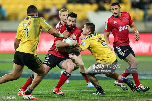 Alapati Leiua of the Hurricanes is tackled by Ardie Savea and TJ Perenara of the Hurricanes during the round 17 Super Rugby match between the...