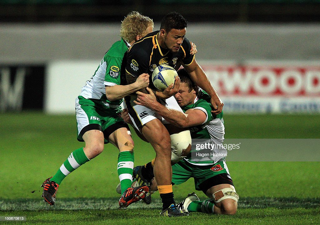Alapati Leiua of Wellington is tackled by Nathan George (L) and Hamish Gosling of Manawatu during the round one ITM Cup match between Manawatu and Wellington at FMG Stadium on August 24, 2012 in Palmerston North, New Zealand.