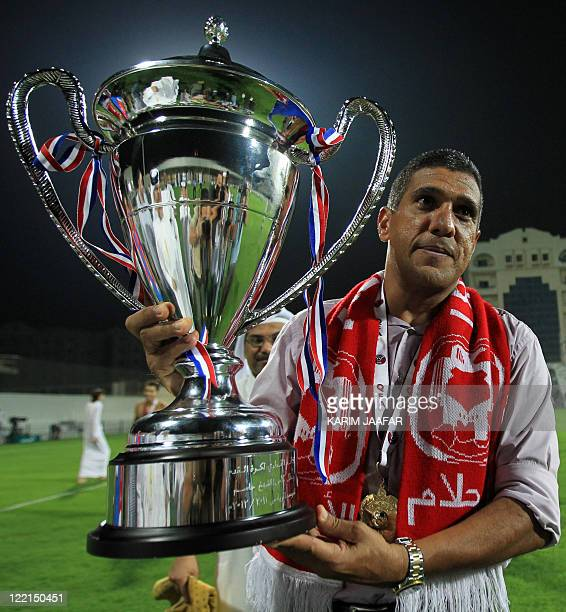 AlArabi's Brazilian coach Paulo Silas holds the trophy after his team beat Umm Salal to win the Sheikh Jassem Cup in the Qatari capital Doha late on...