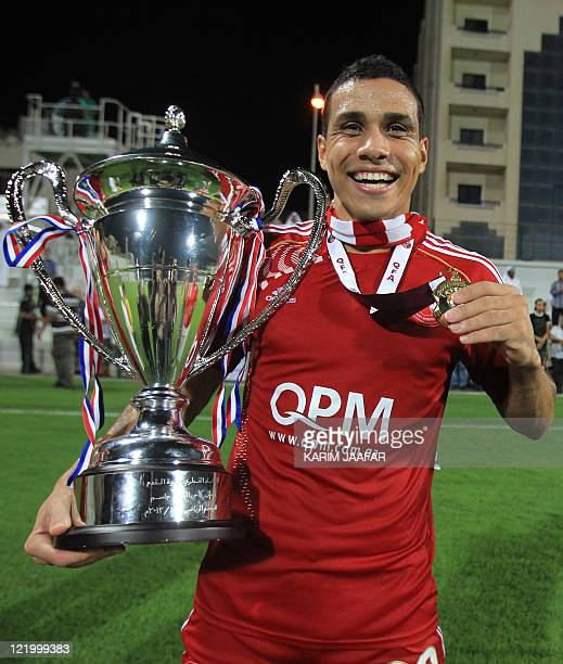 AlArabi's Brazilian forward Wanderley Santos celebrates with the trophy after his team beat Umm Salal to win the Sheikh Jassem Cup in the Qatari...