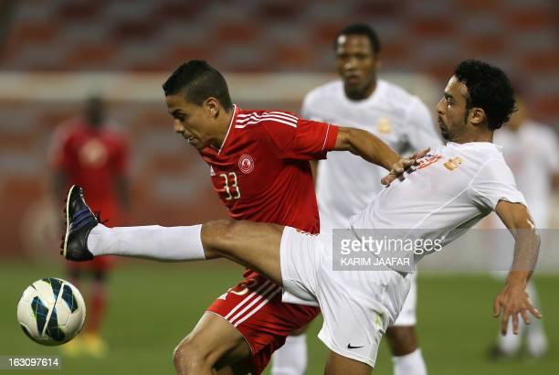 AlArabi's Brazilian forward Wanderley Santos challenges Umm Salal's Othman AlAssas during their Qatar Stars League football match in Doha on March 4...