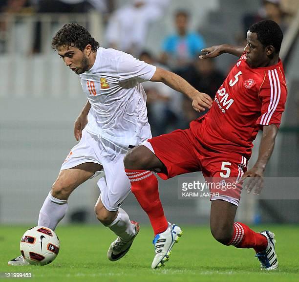 AlArabi's Jawhar alKaabi challenges Umm Salal's Syrian forward Firas alKhatib during their Sheikh Jassem Cup football match in the Qatari capital...