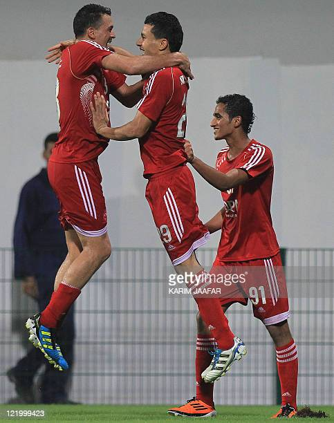AlArabi's Joji Boualem celebrates with his teammates Mohamed Chihani and Abdullah alAraimi after scoring against Umm Salal during their Sheikh Jassem...