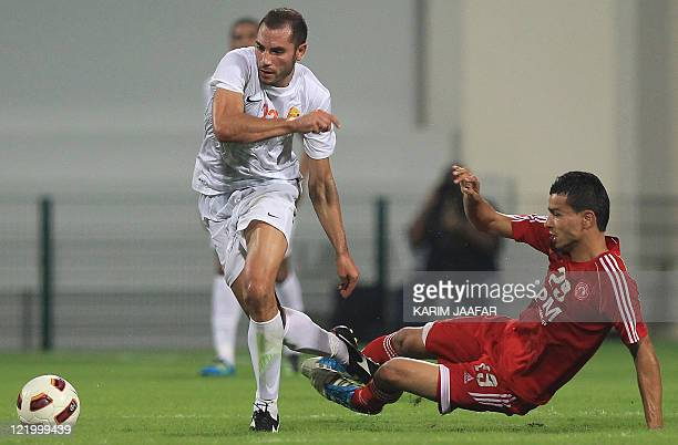 AlArabi's Joji Boualem challenges Umm Salal's Algerian midfielder Mourad Meghni during their Sheikh Jassem Cup football match in the Qatari capital...