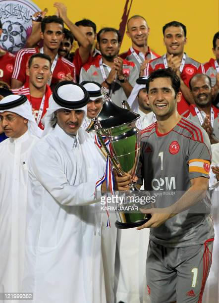 AlArabi's Masud Zeraei receives the trophy from Qatar's Football Association president Sheikh Hamad bin Khalifa bin Ahmed alThani after beating Umm...