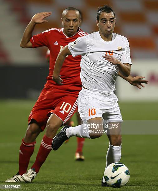 AlArabi's Moroccan player Houssine Kharja challenges Umm Salal's Said Butahir during their Qatar Stars League football match in Doha on March 4 2013...