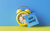 Yellow alarm clock with a blue post it note attached over bright blue background. Save money writes on post it note. Reminder concept. Horizontal composition with copy space.