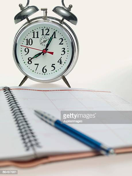 Alarm clock by appointment book and pen
