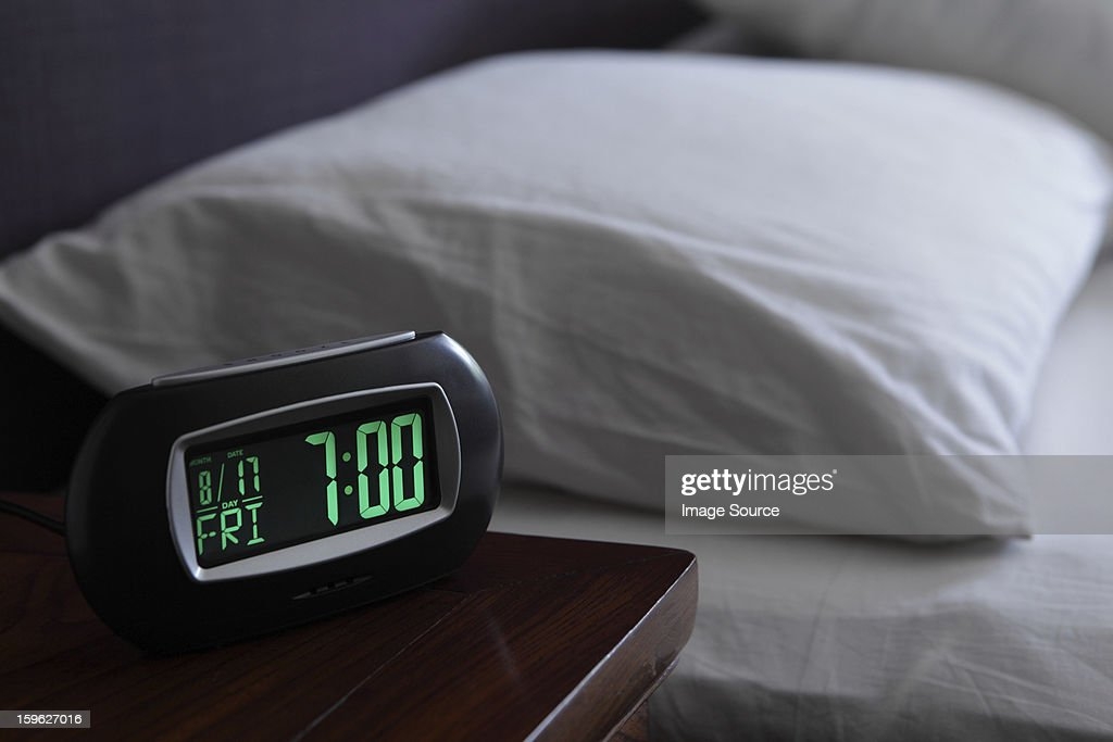Alarm clock by bed : Stock Photo
