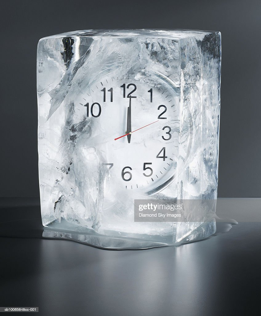 Alarm clock frozen in ice, close-up : Stock Photo