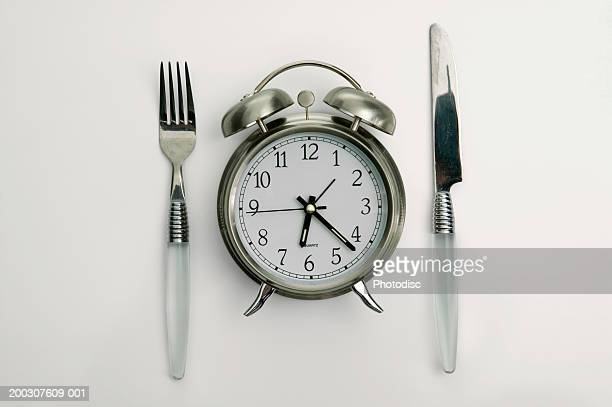 Alarm clock lying between fork and knife