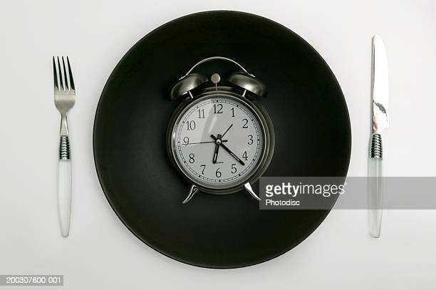 Alarm clock lying on black plate