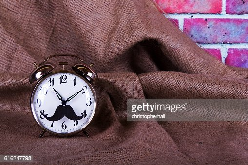 Alarm clock with a black hipster mustache : Stock Photo
