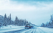 Picture of a semi-truck as it makes its way up the Richardson Highway, in Alaska.  The stunning landscape of the Alaskan winter makes for an amazing display of nature's beauty.  Picture was taken near