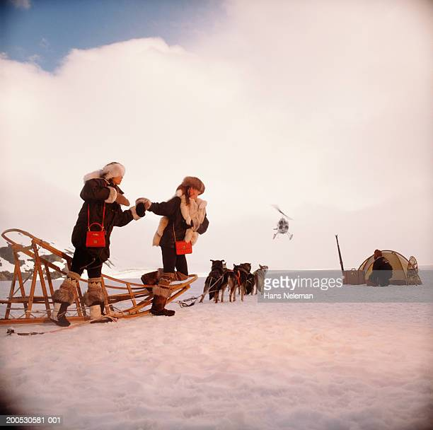 USA, Alaska, two women walking in snow with sled dogs