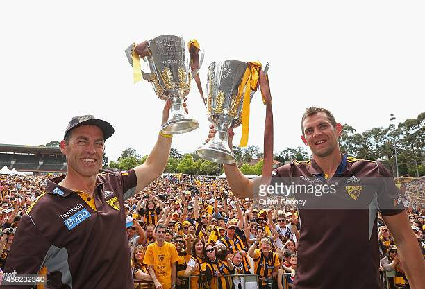 Alastair Clarkson the coach and Luke Hodge the captain of the Hawks hold up the 2013 and 2014 Premeirship Cups at the Hawthorn Hawks AFL team...
