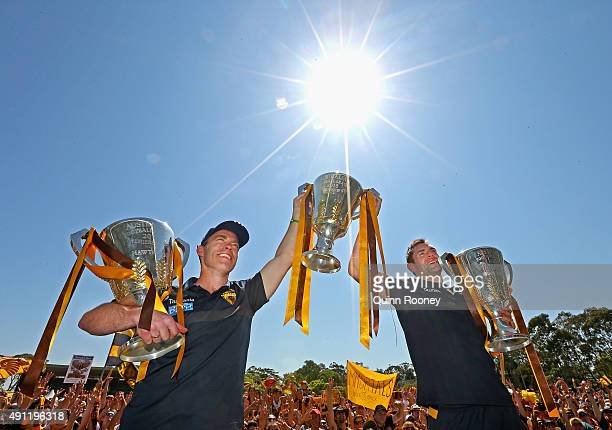 Alastair Clarkson the coach and Luke Hodge the captian of the Hawks pose with the 2013 2014 and 2015 premiership trophies during the Hawthorn Hawks...