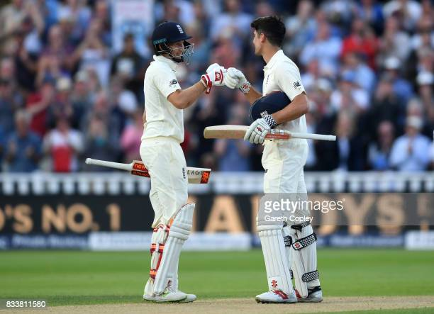Alastair Cook of England celebrates with captain Joe Root after reaching his century during the 1st Investec Test match between England and West...