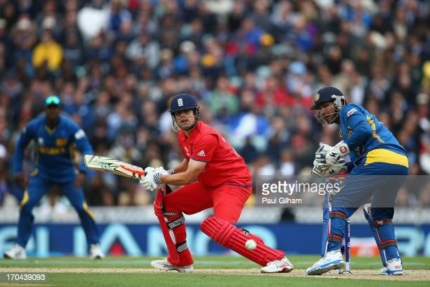 Alastair Cook of England hits out as Kumar Sangakkara of Sri Lanka looks on during the ICC Champions Trophy Group A match between England and Sri...