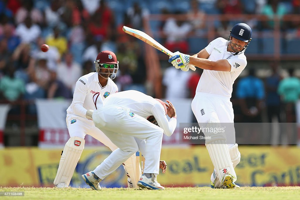 Alastair Cook of England pulls a delivery from the bowling of Devendra Bishoo of West Indies as wicketkeeper Denesh Ramdin looks on and Jermaine Blackwood takes cover during day five of the 2nd Test match between West Indies and England at the National Cricket Stadium in St George's on April 25, 2015 in Grenada, Grenada.