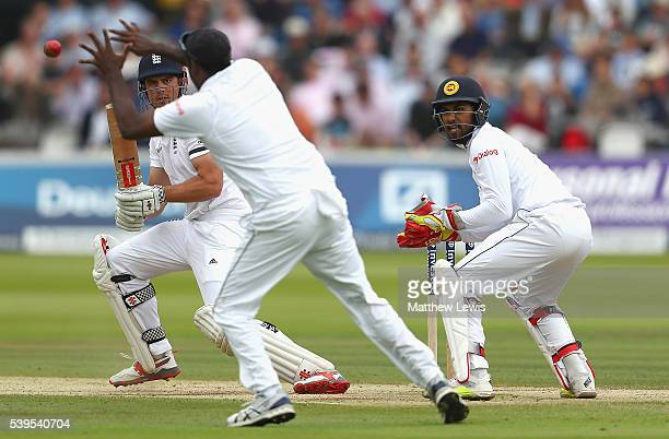 Alastair Cook of England reverse sweeps the ball towards Angelo Mathews of Sri Lanka as Dinesh Chandimal looks on during day four of the 3rd Investec...