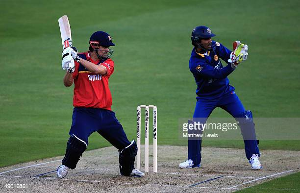 Alastair Cook of Essex Eagles hits the ball towards the boundary against the Sri Lanka Dinesh Chandimal of Sri Lanka looks on during a Tour match...