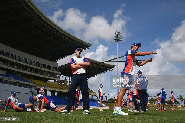 Alastair Cook stretches as James Tredwell looks on during the England nets session at the Sir Vivian Richards Stadium on April 11 2015 in Antigua...