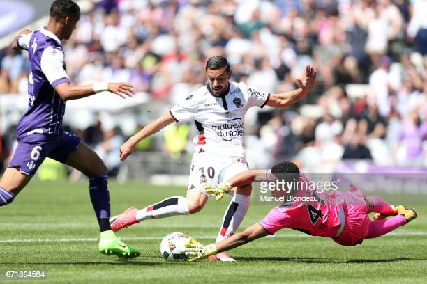 Alban Lafont of Toulouse makes a save under pressure from Mickael Le Bihan of Nice during the Ligue 1 match between Toulouse FC and OGC Nice at...