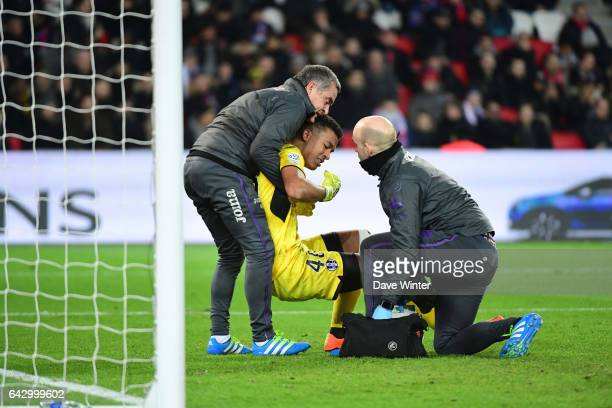 Alban Lafont of Toulouse receives attention during the French Ligue 1 match between Paris Saint Germain and Toulouse at Parc des Princes on February...