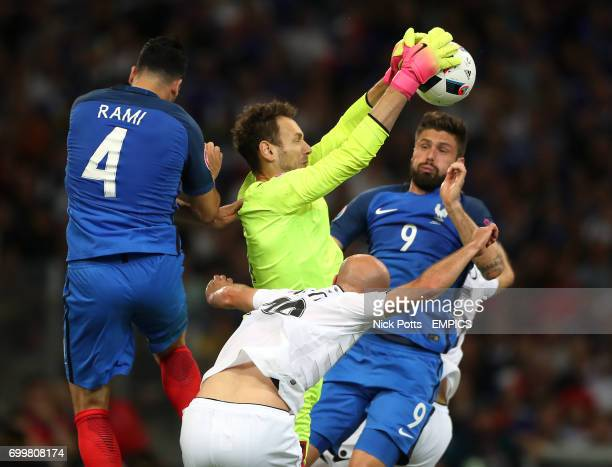 Albania goalkeeper Etrit Berisha claims the ball under pressure from France's Olivier Giroud and Adil Rami
