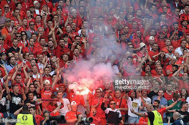 Albania supporters light a flare during the Euro 2016 group A football match between Albania and Switzerland at the BollaertDelelis Stadium in Lens...
