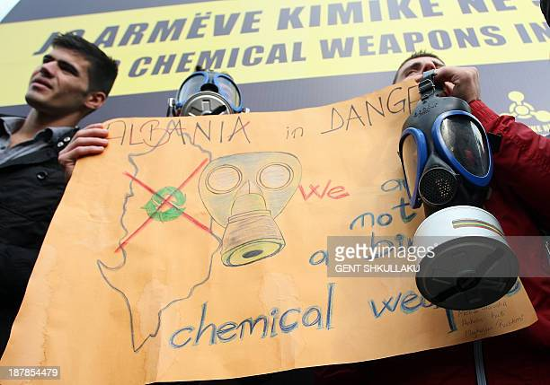 Albanian environmental activists hold a placard outside the government building in Tirana on November 13 2013 during a protest against the...