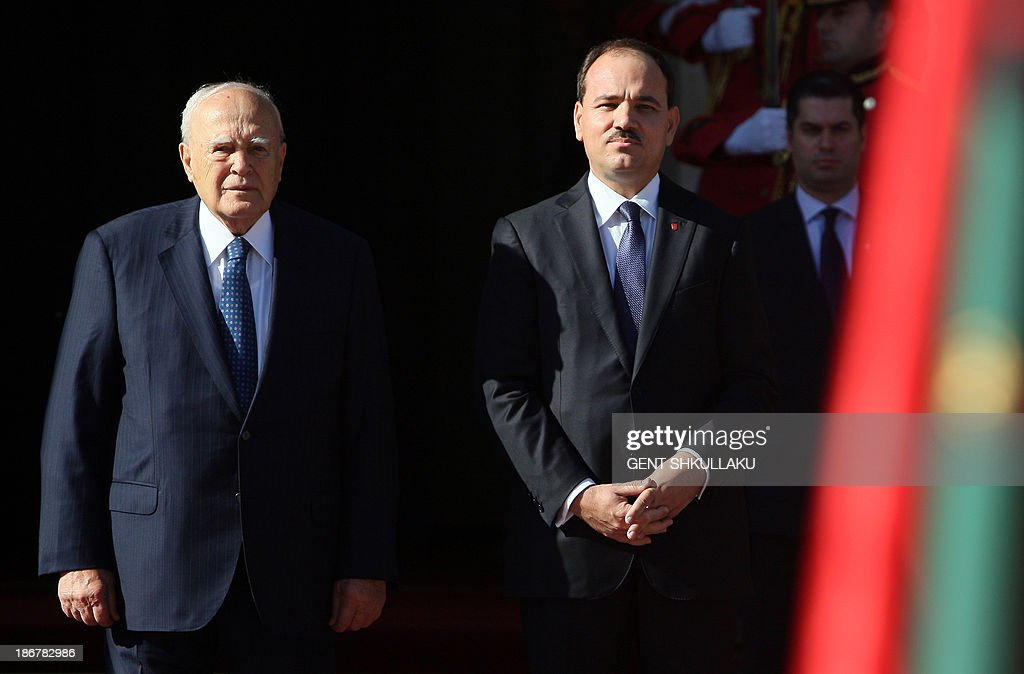 Albanian President Bujar Nishani (R) and his Greek counterpart Karolos Papoulias (L) listen to the national anthems during a welcoming ceremony in Tirana on November 4, 2013. Greek President Papoulias arrived in Tirana on 3 November for a three-day official visit to Albania.