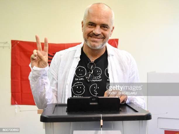 Albanian Prime Minister Edi Rama flashes a victory sing as casts his ballot at a polling station in the village of Surrel near Tirana during a...