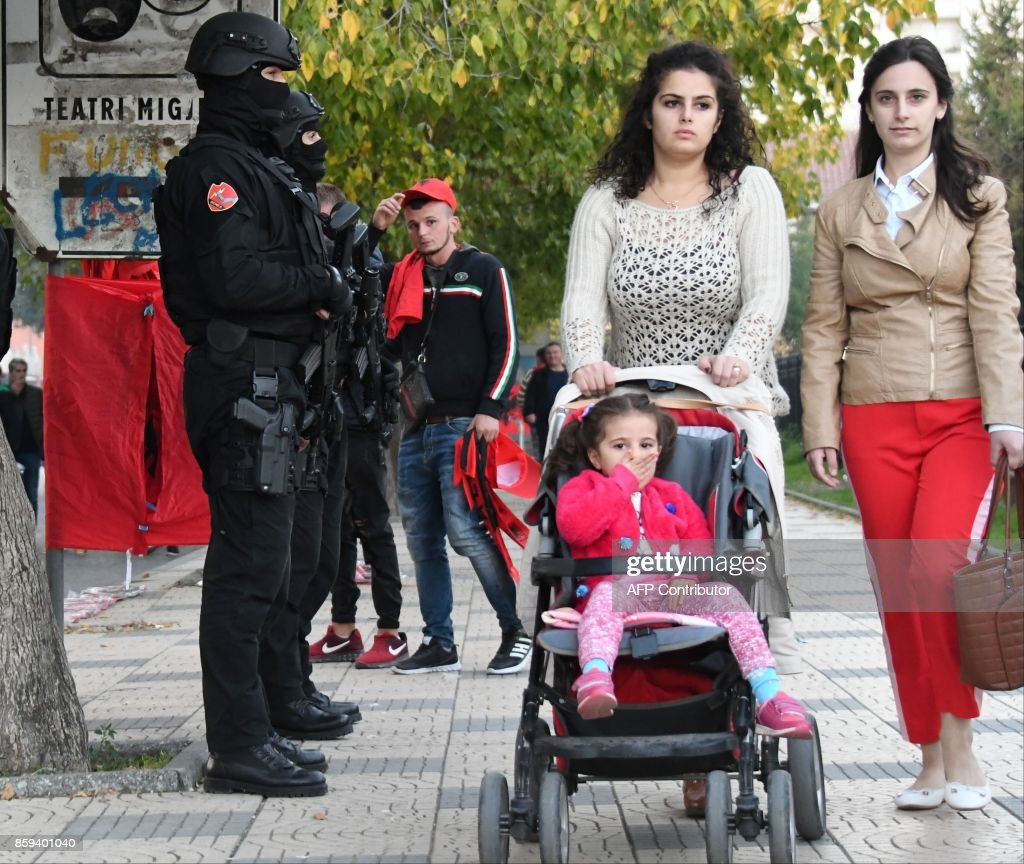 Albanian special policemen (L) stand guard as residents walk past, near the Loro-Borici stadium in Shkoder, prior to the FIFA World Cup 2018 qualification football match between Albania and Italy on October 9, 2017. / AFP PHOTO / Gent SHKULLAKU