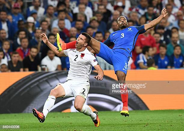 Albania's defender Andi Lila and France's defender Patrice Evra are caught up as they vie for the ball during the Euro 2016 group A football match...